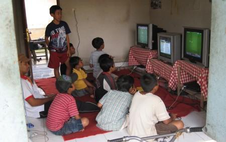 Balinesische Kinder an der Spielkonsole